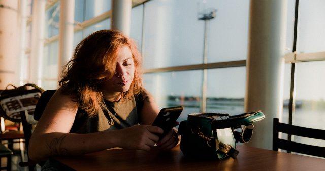 Woman using phone at airport